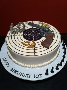Cake was a 60th birthday cake for a male who loved to shoot in his spare time. Pistol and bullets were made out of fondant and painted with silver and gold edible paint. Target was made using edible icing sheets.