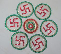 Made up of red-stone swastikas surrounded by a circle of green stones. The central piece is intricate and includes red, green, golden stones and pearls.