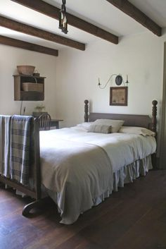 Shaker Style Minimalism; Beige Linens, Vintage Wool Blankets, and Carved Wood Bed.
