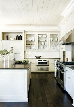 Dark wood floors, contrasting white cabinetry dark bench top