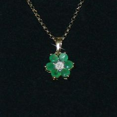 This pendant features a flower design with dazzling emerald stones and a single genuine diamond. This necklace is crafted of highly polished 14k gold over 925 sterling silver and would make a lovely addition to any jewelry collection. | eBay!