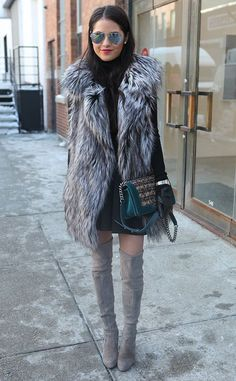 Shop this look on Lookastic: http://lookastic.com/women/looks/sunglasses-vest-turtleneck-watch-skater-skirt-over-the-knee-boots-gloves-satchel-bag/7766 — Grey Sunglasses — Grey Fur Vest — Black Turtleneck — Silver Watch — Black Skater Skirt — Grey Suede Over The Knee Boots — Black Leather Gloves — Dark Green Leather Satchel Bag