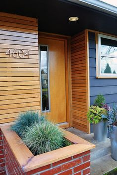 use wooden trim to echo roof color, add wood panel wall to the porch and use a wood colored door, echoeing roof color, then add dark blue accents on railing and side of house