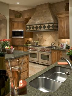 Rustic tile, side-by-side ovens under huge vent hood; Kitchen by Debra May Himes