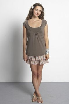 Joelle Jersey Tee by Mothers en Vogue  Designed with a long and relaxed silhouette, and constructed in bamboo with a hint of spandex for optimal comfort and flexibility.     Finished with delicate piping detail and front gathers at neckline.     Constructed with neckline nursing access: The scooped neckline is designed lower so it can be conveniently pulled downwards to nurse while an inner chest lining functions as a modesty cover.    Shown in Cobblestone. *image provided by Mothers en…