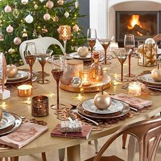A beautiful table, a fireplace and a Christmas tree, everything is ready to make you feel at home. #ShopNow -- Click link on @maisonsdumonde -- #Copper #table #christmas #tree #cute #chimney #yummy #inspiration #luminous #glass #plates #chairs #apple #mymdm #maisonsdumonde #myMDMxmas