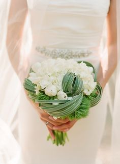 white hydrangea, white tulips and lily grass tucks. The movement of the gathered lily grass is visually stunning. Beautiful way to make the more traditional flowers offbeat and unique!