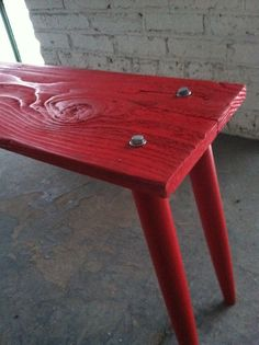 I made a bench! ... 1 piece of reclaimed barn wood, 4 legs off of a Good Will sewing table, some lag screws, and red Behr combo paint+primer, and you have some extra seating :)