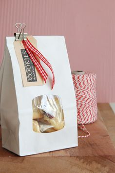 LOVE this idea of using white bags and then dressing them up with a cute tag and ribbon. Swap out the metal clip for a mini wooden clothespin if you prefer. #holidayentertaining