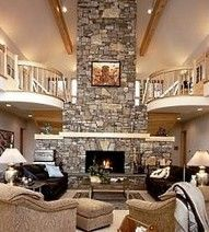Seating grouped around the tall fireplace. Love the flanking balconies, but I think the art on the chimney should be much larger.