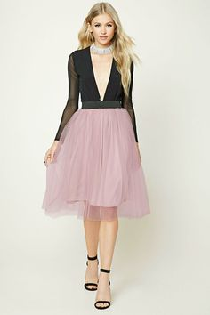 A knit skirt featuring a shirred tulle mesh overlay, a contrast elasticized waistband, and a knit underlayer skirt.