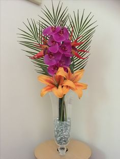 DIY Artificial Tropical Floral Arrangement. Areca Palm, Orchid, Lilly & Bird of Paradise in a footed glass vase. Exotic colours.
