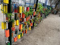 geniale idee, nicht nur für schulhofzäune! milchtüten bunt bekleben/bemalen und bepflanzen... und mit kabelbindern an den zaun.