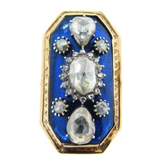 Rare Georgian period blue glass back 15ct. yellow gold engraved frame ring. The center is set with an oval rose cut measuring approx. 8.9 mm. x 5.7 mmm. surrounded by 16 small rose cuts with 2 teardrops set north and south with 4 accents. Sixe 6 1/2 circa 1830.