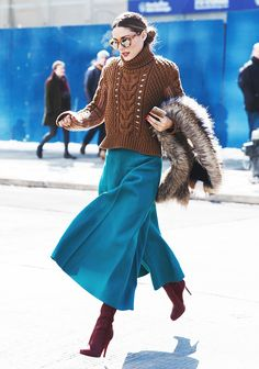 Olivia Palermo wears a cable-knit sweater, turquoise maxi skirt, red boots, mirrored sunglasses, and a fur stole