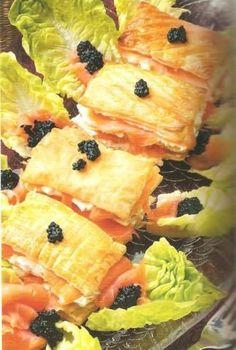Mil hojas de salmon • 1 huevo batido • 1 paquete de masa de hojaldre • 1 tarrina de queso de untar sabor salmón • 120 Gr. de salmón ahumado • decorar por arriba con lo que se quiera: huevas de salmon, de mujol, etc.... 1. Cortar 4 rectangulos de hojaldre sin estirar Pintar con huevo batido, hornea a 200º durante 15 minutos 2. Unta con el queso, coloca una loncha de salmón y cubrelo con la tapa de hojaldre, decora con lechuga y con las huevas. salmón*: