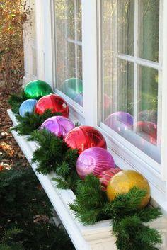 boules de Noël multicolores et branches vertes ornent la fenêtre blanche
