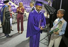 Carson Huey-You, 14, smiles as his 10-year-old brother Cannan shows him one of his graduation gifts, a Hobbit Lego set, after Carson received a bachelor's degree in physics at the Texas Christian University commencement held in Fort Worth, Texas, on Saturday, May 13, 2017. Huey-You, the youngest student ever to attend TCU, also double minored in math and Chinese since enrolling in 2013. (Louis DeLuca/The Dallas Morning News via AP)
