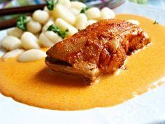 Porce kuřete pečené na cibulovém základu s kořením, podávané přelité smetanovou omáčkou.