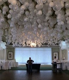 White ballon highlighted by light hanging  from the ceiling