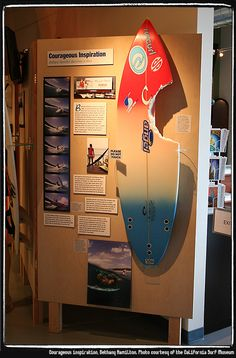The display about Bethany's shark attack at a museum. Includes the board she was riding on and the swimsuit she was wearing.
