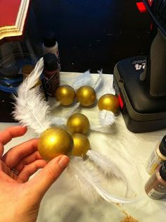 make my own- styrofoam ball, spray paint gold, jam white feathers in there