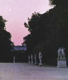 pink purple sky crescent moon statues trees