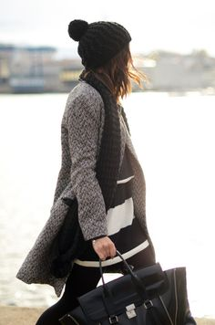 pom pom hat, gray winter coat, black satchel
