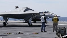 An X-47B drone taxis in front of an F/A18 fighter plane as it is prepared for take off: The aircraft is as yet not equipped with military hardware, but is designed for ample space to accommodate bombs and surveillance equipment. Eliminating the need for life-support equipment frees up the room for two 2,000lb bomb bays