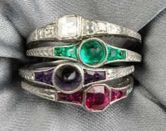 """Set of Four Art Deco Platinum Gem-set Acrostic Stacking Rings, T.B. Starr, set with a square-cut diamond, cabochon emerald, cabochon amethyst, and fancy-cut ruby, all with conforming shoulders, spelling out """"DEAR"""", engraved accents, approx. size 5 1/2, signed. At Skinner. Love these!"""