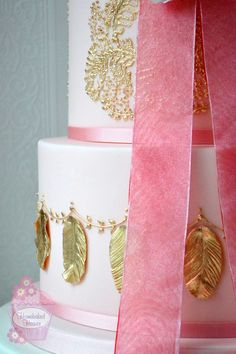 "With their sumptuous fabrics, oh-so-pretty lace, jewel-like colours {and sheer opulence!} I would love, one day, to wear a dress made by Joanne Fleming Design. Cue fancy night out. Vow renewal? For now though, here's my latest wedding cake design, ""Evelyn"", inspired by two of Joanne's exquisite 1920s flapper-style creations, iced in one of this year's bridal Pantone colours, Rose Quartz, and decorated with sugar tree peony, cornflowers, gilded lace brush embroidery and sugar feathers."