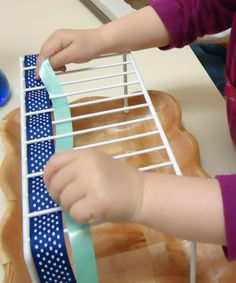 To the Lesson!: Back to the Basics This blog post shows all kinds of Montessori materials in use, but I was most excited by the use of a kitchen shelf-extension rack to learn the basics of weaving! Great idea!