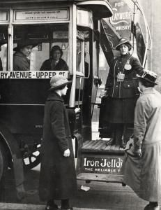 First World War London General Omnibus Company women bus conductor on service. The conductor stands on the bus platform, with passengers about to board; others can be seen sitting inside the bus.    Unknown photographer, 1916 - 1919