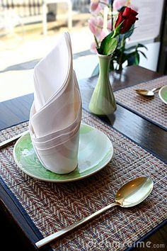 images of oriental folded napkins   Table setting in an oriental restaurant with beautiful folded napkin.