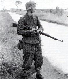 A Panzer Grenadier from 12th SS-Hitlerjugend in France. He is wearing the distinctive M44 DOT pattern tunic and trousers. His helmet has the bread bag straps around it to loop foliage through for camouflage. The recognizable jackboots were replaced by ankle boots with 'gamaschen' or gaiters.