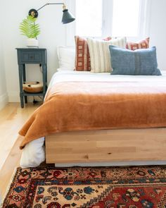 This bedroom has major fall goals. The earthy tones in the vintage area rug at the foot of the bed, the terracotta throw blanket, and the rust mudcloth pillows paired with Turkish kilim pillows. All create the coziest space.