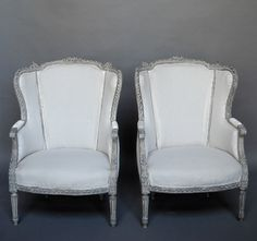 "Pair of Swedish Bergeres, #21-23 - Pair of Gustavian style bergeres â oreilles, Sweden circa 1860. Beautifully carved frames with traces of the original gilding and upholstered elbow rests.  H:38½"" (seat, 16""), W:26"", D:27""."