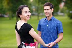 © Nicole Dixon Photographic Columbus Ohio outdoor engagement photos. Bride in cute skirt with her groom to be in the park and Columbus Hilton. Lush outdoor green park.