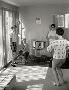 """Before P90X & Insanity Workouts….there was Jack LaLanne!  1960 """"Airline hostesses Sue Pharris, Sharon Moore and two other women watching the Jack LaLanne physical fitness show and exercising."""" From photos taken to illustrate the Look magazine article """"TV's Nature Boy."""" Among this picture's mid-century markers: Polka-dots, a pole lamp, rabbit ears, flip-flops, sliding glass doors."""