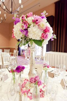Love the tall candle stick with arrangement on top, as well as rose petals around the bottom.