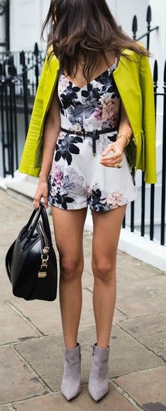 Floral romper, gray booties, neon coat, basic black purse all come together to make a chic transitional summer outfit.  The pairing is unexpected with the bright coat and patterned romper making it look like a high fashion outfit.  Remember to mix and match pieces that don't obviously go together to create high fashion street style outfits.