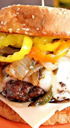 1 med. onion...2 jalapenos...4 T. butter, divided...1 lb. hamburger...2 T. Worcestershire sauce...1 T. liquid smoke...1-1/2 oz. pkg. taco seasoning mix...Monterrey Jack or Swiss cheese...Hamburger bun...banana peppers
