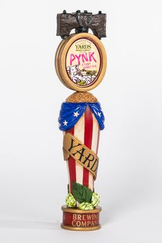 """Party A-Philly-ation""—Brian Cook. It has a old political campaign theme. The Liberty bell is replaced with a double sided Yards label, in a gold oval. The label sits atop an antiqued red and white pull down banner, with blue bunting on the sides.  The banner is based in hops and leaves and topped with grains.  Regally wrapping the banner is a gold ribbon with a Yards logo on the front and "" est. 1994"" on the back. The red drum base completes the handle with ""Brewing Company"" and gold stars."