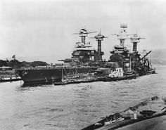 USS Tennessee in the aftermath of the Pearl Harbor attack. Next to her lies USS West Virginia sunken in shallow water. Both would be repaired, rebuilt and star in a battleship gunfight later in the war, the battle of Surigao Strait.