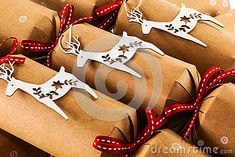 Simple brown card Christmas crackers with white riendeer decorations and red ribbons