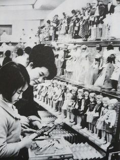 A mother and daughter shop for American dolls at a department store, Japan, 1966.  Ironically the dolls on display were made by American firms using factories in Japan.  On the top shelf are Barbie dolls by Mattel, while on the bottom are Tammy dolls made by Ideal (with a more innocent stylized face that was more in line with Japanese taste than the more European Barbie).  Both, though, would be outpaced by the introduction of Japan's first native fashion doll Licca-chan, made by Takara in…