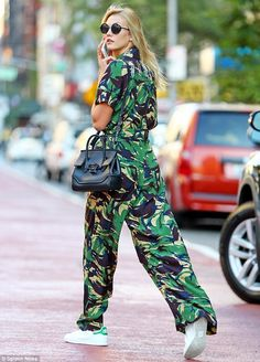 Bold fashion statement: The 24-year-old supermodel stayed comfy as she teamed the wide-legged jumpsuit with a pair of white trainers with a pop of green on the backside