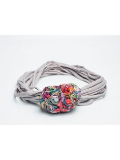 Galería paraíso. Tocado o gargantilla de cintas de algodón elástico. En el centro una flor tipo clavel.