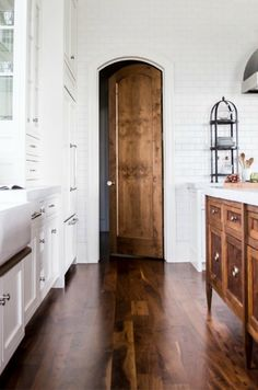 white kitchen with a stained hardwood floor and wood island and door - stunning!
