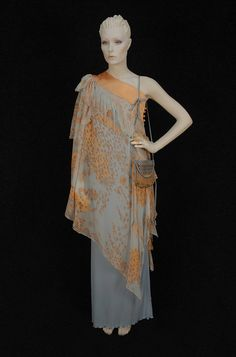 """ZANDRA RHODES ONE-SHOULDER GOWN and EVENING BAG, c. 1980. Powder blue jersey knit, the bodice top having a wide angled band of topstitched apricot satin above a chiffon asymmetrical tunic printed in apricot and brown stylized desert landscape, side self button closures. Unlabeled. Matching printed and pleated satin bag with label """"Zandra Rhodes London"""". B-36, L-59. Bag 5 1/2 x 7. Excellent. $1,320."""